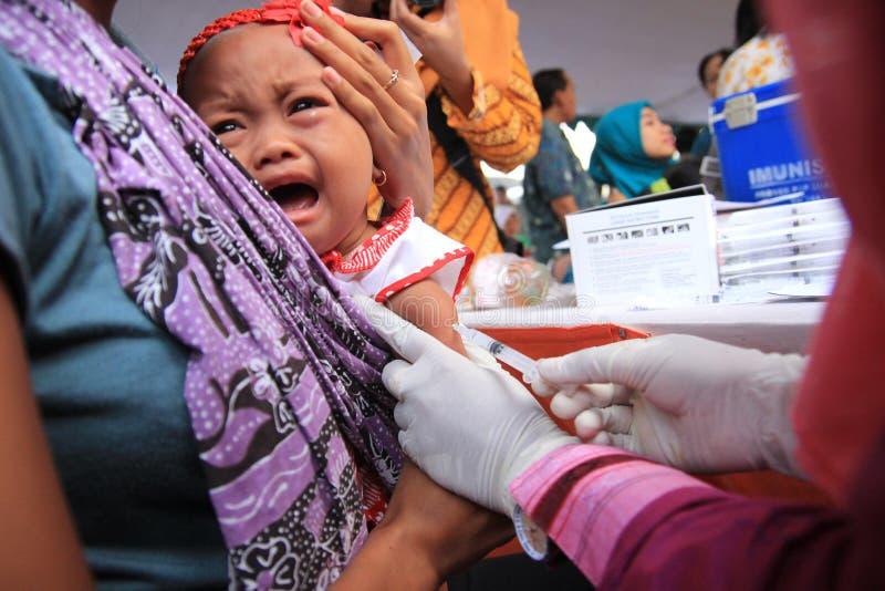 Surabaya Indonésia, pode 21, 2014 um trabalhador do setor da saúde está dando tiros da imunização a uma criança fotografia de stock