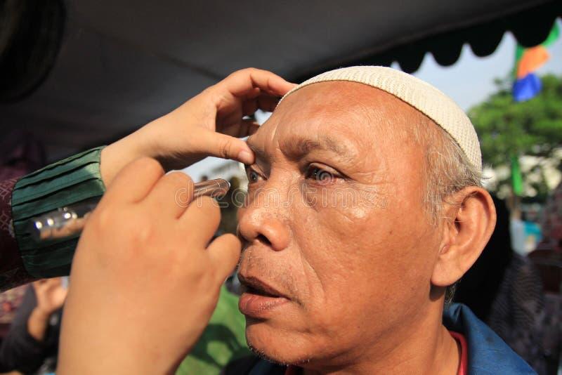 Surabaya Indonesië, kan 21, 2014 een gezondheidsarbeider controleert de ogen van de patiënt royalty-vrije stock afbeeldingen