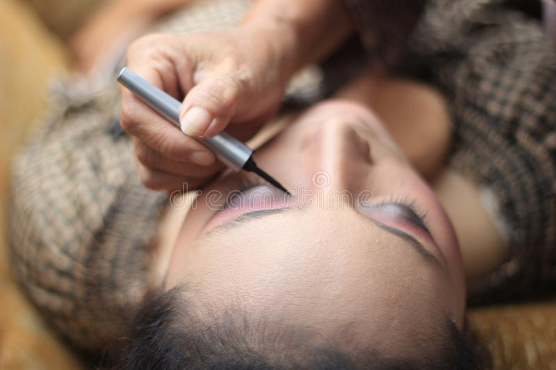 Surabaya indonesia. June 17, 2017. A makeup artist is busy putting on a client`s face royalty free stock image