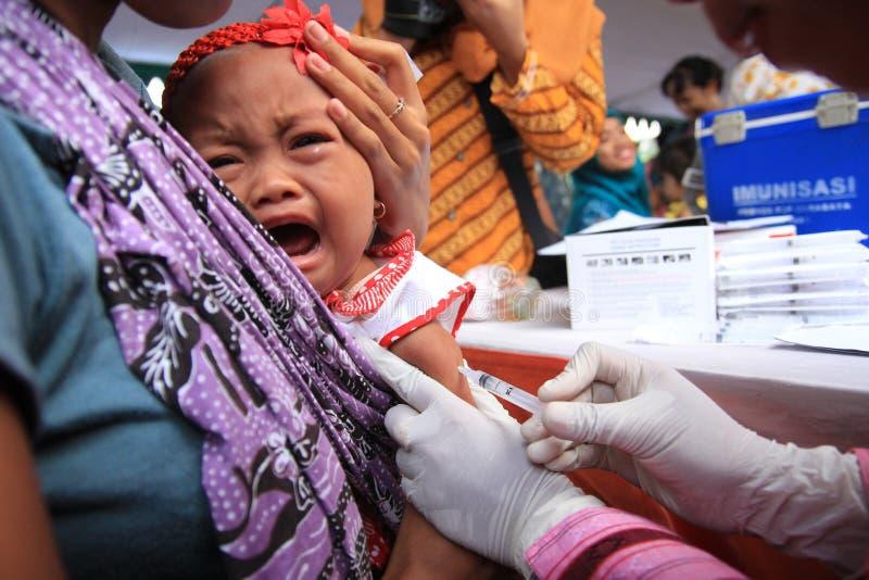 Surabaya Indonesia, puede 21, 2014 un ayudante de sanidad dio vacunaciones a los niños imágenes de archivo libres de regalías