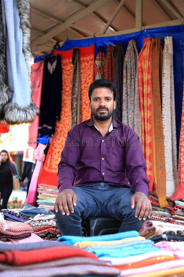 Surajkund, Faridabad, Haryana, India - February 14, 2020 - Seller with Indian clothing during the 34th Surajkund International. Crafts Mela. The festival has stock images