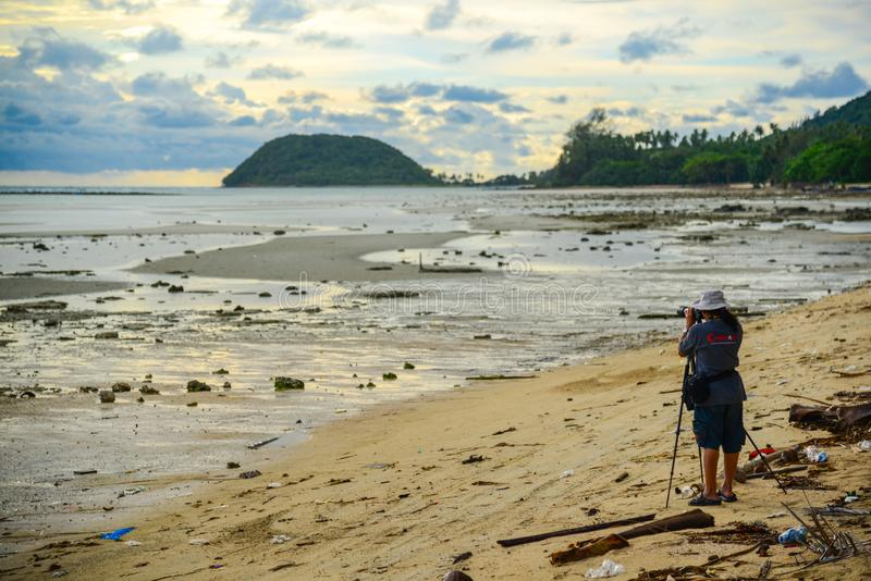 Photographer on dirty beach shooting view of sea and sky. Surat Thani, Thailand - May 25, 2013: Photographer on dirty beach shooting view of sea and sky in Surat royalty free stock photo
