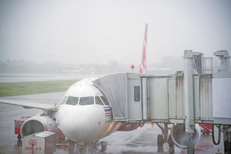 SURAT THANI, THAILAND - November 11: In heavy rain, AirAsia to land at Surat Thani Airport, safety and bridge connecting the aircr stock photos