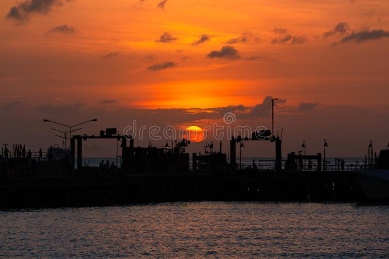 Suratthani, Thailand - January 7, 2019: Sunset in the sea at Nathon The ferry pier has tourists to sit on the pier. Big sun stock images