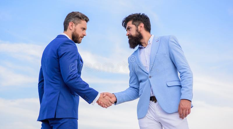 Sure sign you should trust business partner. Men formal suits shaking hands blue sky background. Business deal approved royalty free stock photo