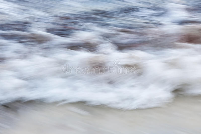 Surf abstract. Ocean waves crashing on sandy beach abstract, in-camera motion blur royalty free stock images