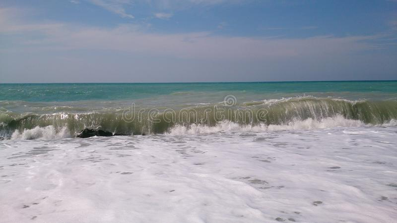 Sea surf at the beach. Surf at the beach in summer day against blue sky and white clouds royalty free stock photos