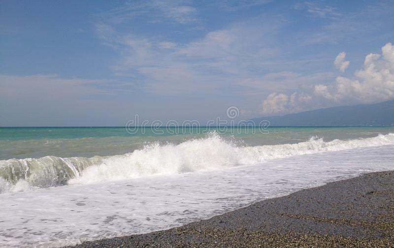 Sea surf at the beach. Surf at the beach in summer day against blue sky and white clouds stock photos