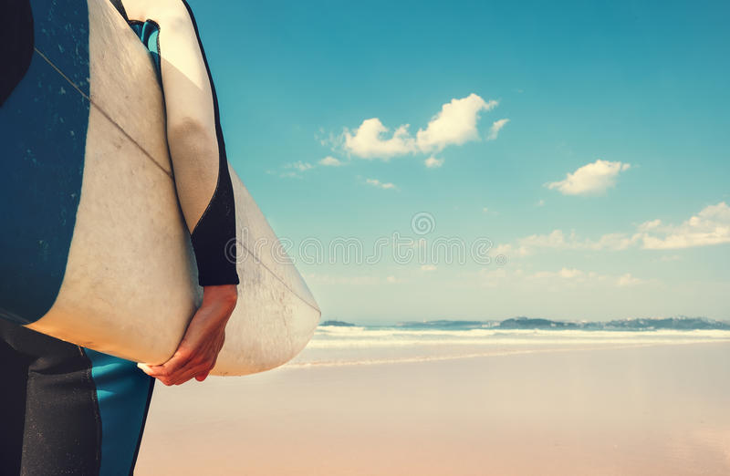 Surf board in surfer`s hand close up image with oceans waves vie stock photos