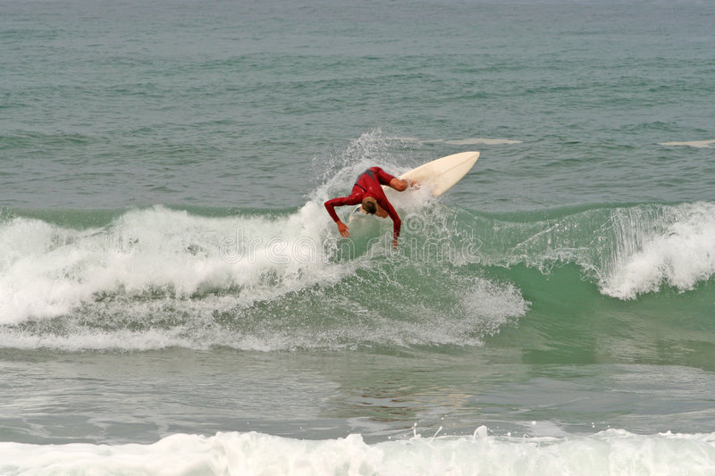 Surf boarder in action. Scenic view of male surf boarder riding waves at sea stock photo