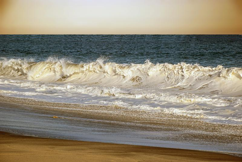 Surf breaks on the beach stock photography