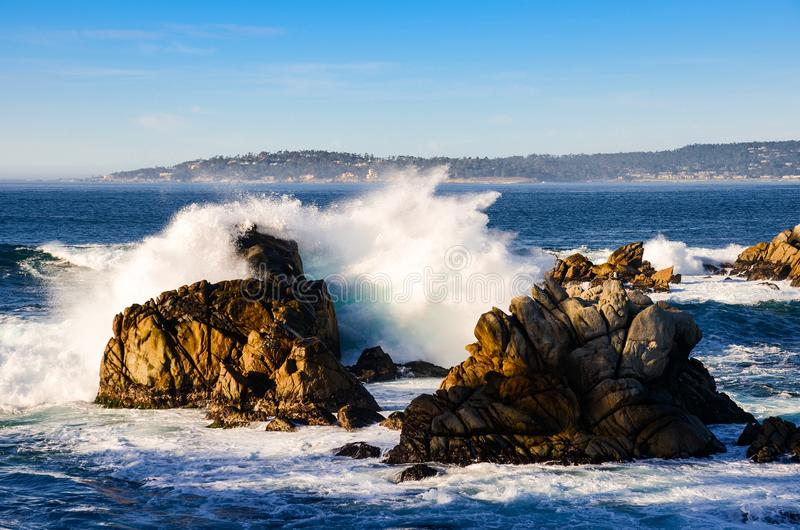Surf breaking against rocks along the California coast. Surf breaks on rocks at Point Lobos overlooking Carmel Bay and the Monterey Peninsula on California`s royalty free stock photography