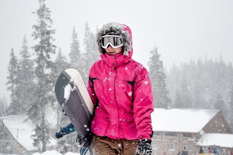 Surf des neiges de participation de jeune femme images stock