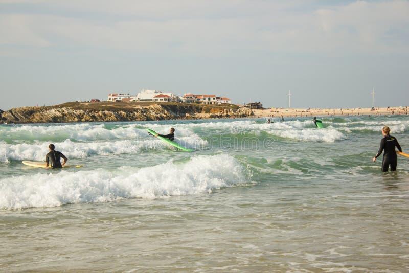Surf'in en Baleal durante una marea áspera con el pequeño pueblo de Baleal en el horizonte foto de archivo libre de regalías