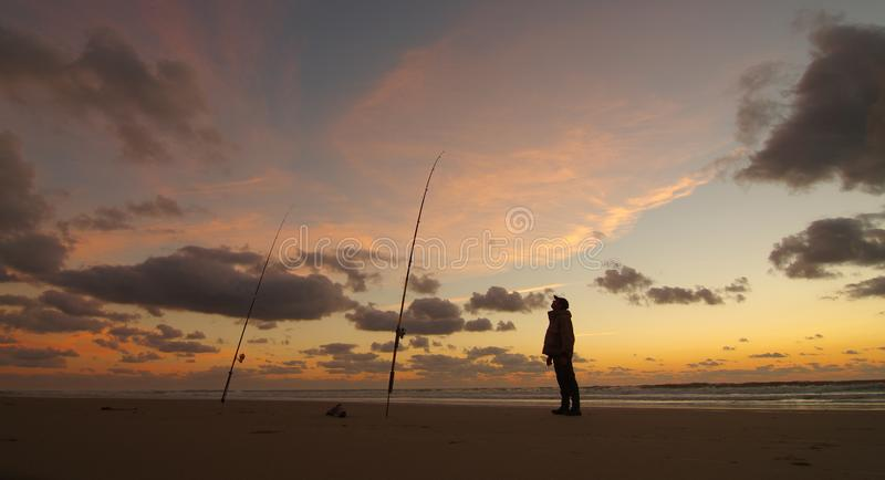 Surf fishing at sunset stock image