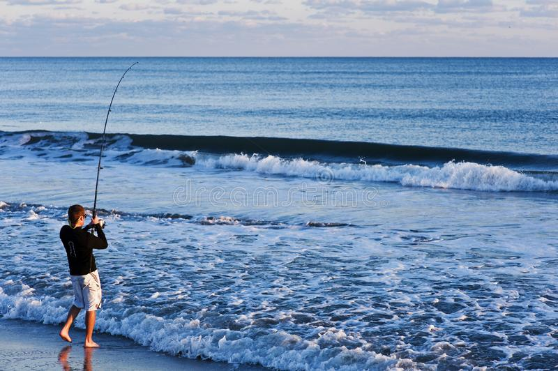 Surf fishing on an ocean beach. Young man fishing and catching a fish on a calm beach in the atlantic ocean royalty free stock images