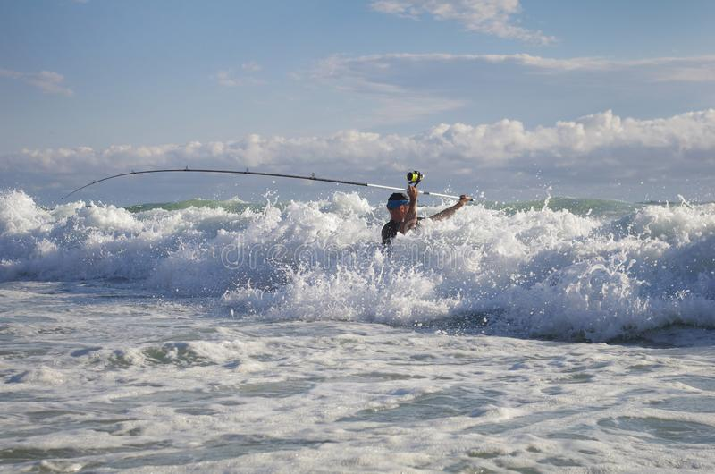 Surf fishing scene. Surf fisherman into the waves trying to cast the line stock images