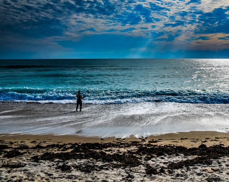 Surf Fishing in the Shadows of the Clouds. A seascape of a man surf fishing on a Florida beach as sunbeams and shadows fill the sky stock photo