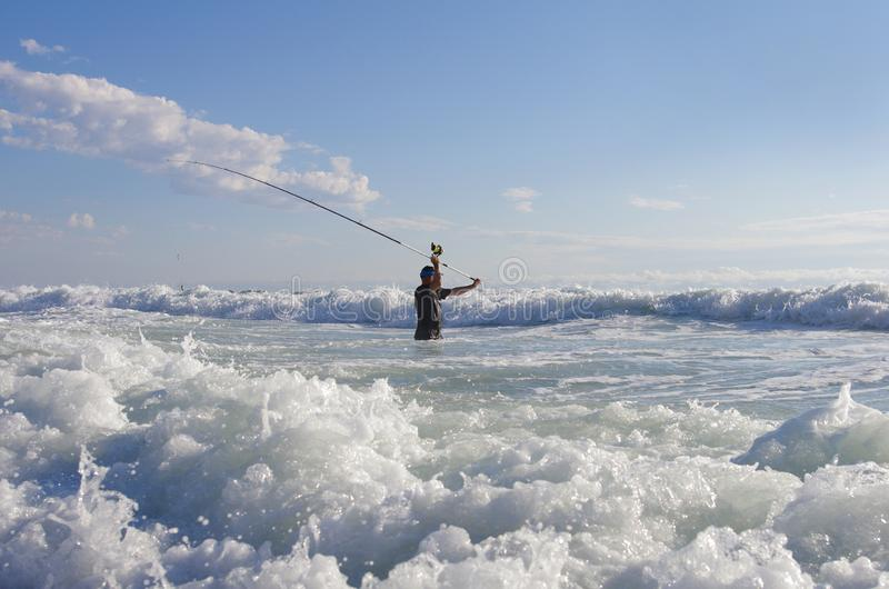 Surf fishing in the waves stock image