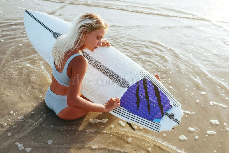 Surf girl with long hair go to surfing. Young surfer woman holding blank white short surfboard on a beach at sunset or sunrise royalty free stock photos