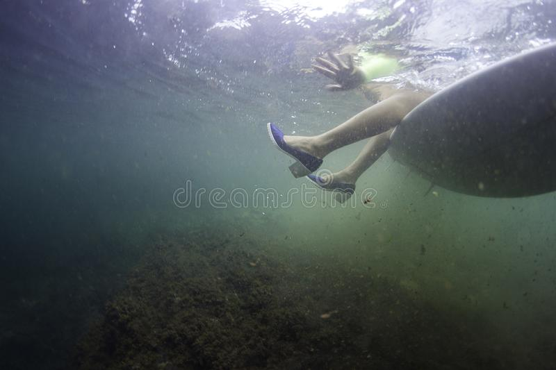 Surf girl sitting on a surfboard with shoes underwater stock photography