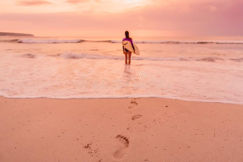 Surf girl with surfboard go to surfing. Surfer woman on a beach at sunset or sunrise. royalty free stock images