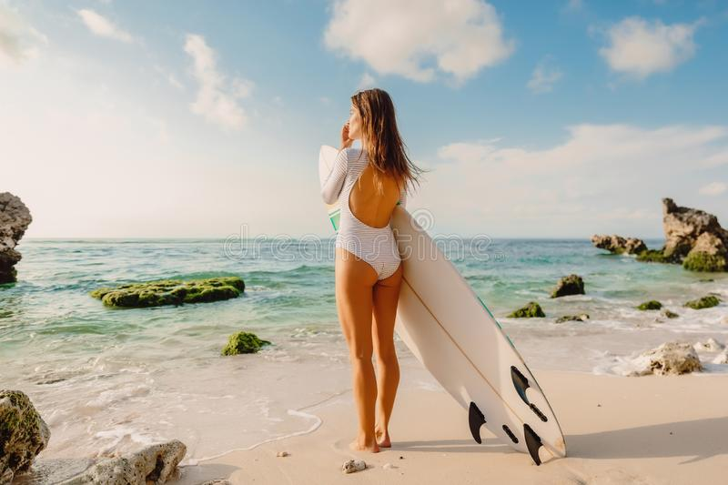 Surf girl with surfboard looking at ocean. Beautiful surfer woman at beach. Surf girl with surfboard looking at ocean. Beautiful surfer woman royalty free stock image