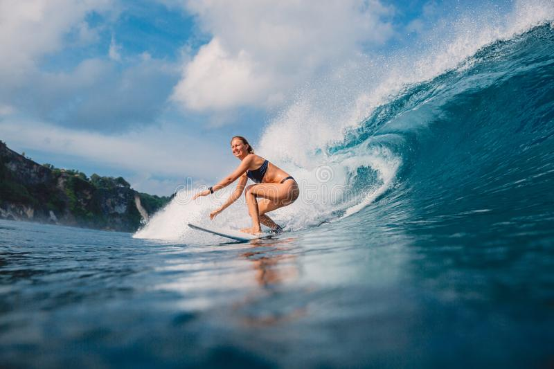 Surf girl at surfboard ride on barrel wave. Woman in ocean during surfing royalty free stock photography