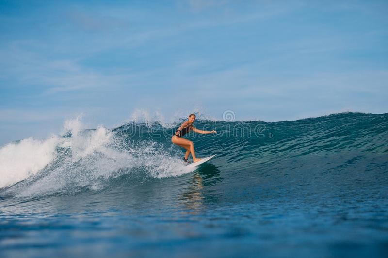 Surf girl at surfboard ride on barrel wave. Woman at ocean wave royalty free stock images