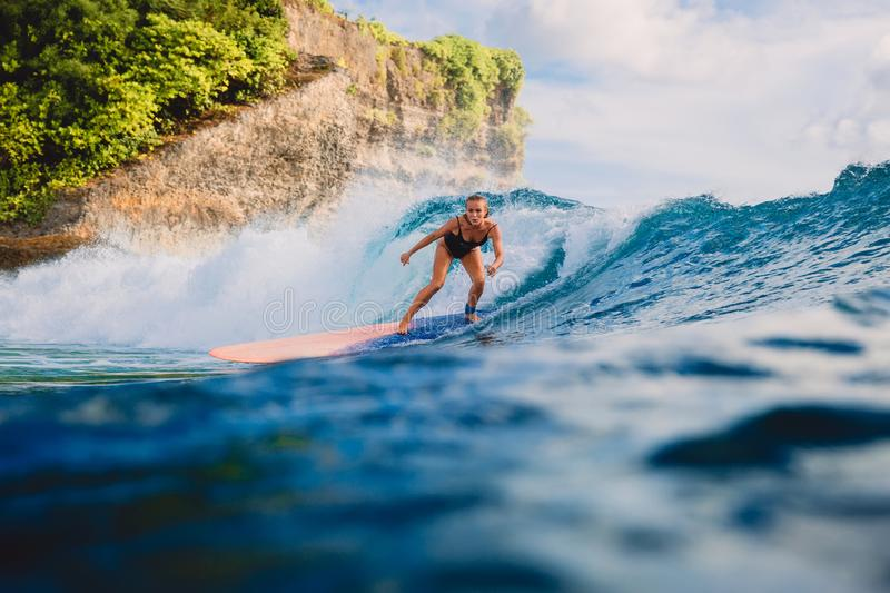 Surf girl on long surfboard. Woman in ocean during surfing. Surfer and ocean wave royalty free stock photo
