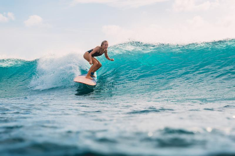 Surf woman on surfboard during surfing. Surfer and ocean wave. Surf girl on surfboard. Woman in ocean surfing royalty free stock image