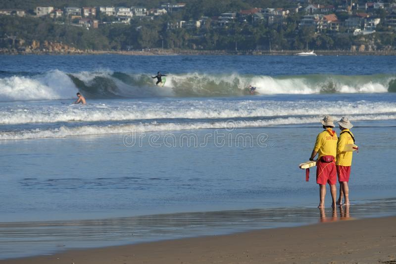 Surf Life Savers. Two Surf Life Savers watching Manly Beach Sydney Australia royalty free stock photo