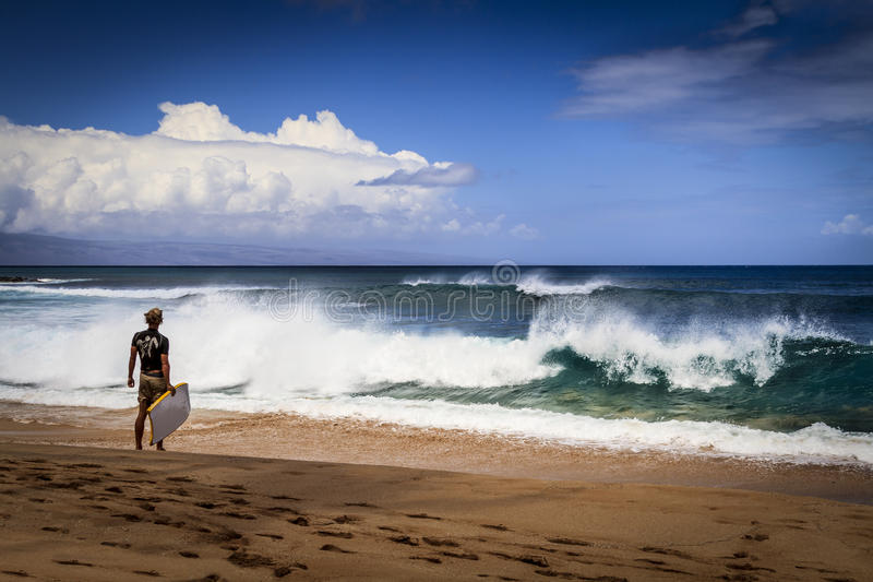 Surf at Napili Bay, Maui, Hawaii. This lone boogie-boarder checks out the surf with the island of Lanai royalty free stock photo
