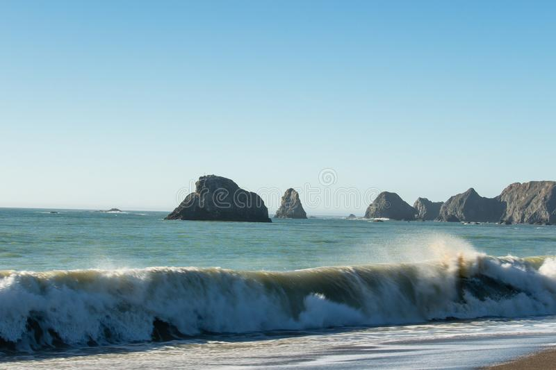 Surf from the Pacific Ocean breaking on the beach at the Russian River mouth stock image