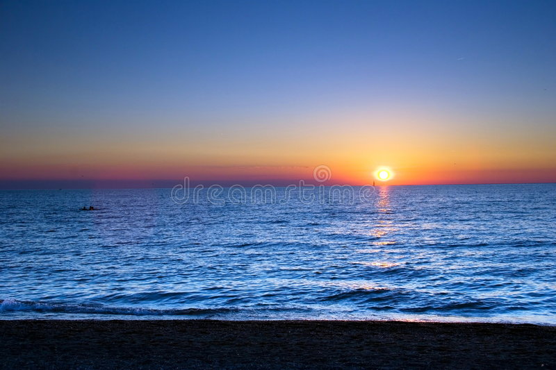 Surf and Sail. Sailboat in the Sunset royalty free stock image