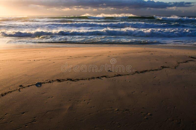 Surf, sand, and sunrise at the beach. Surf, sand, and a glowing sunrise at the beach royalty free stock photos
