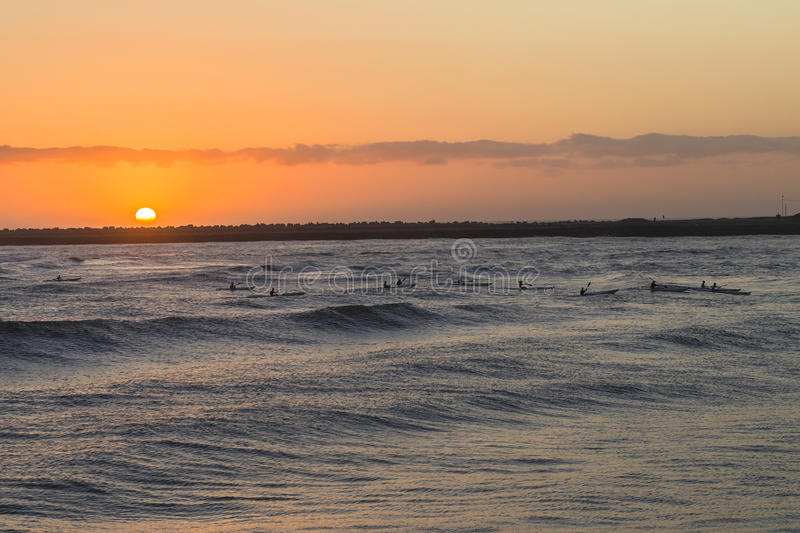 Surf-ski Paddlers Ocean Sunrise stock image