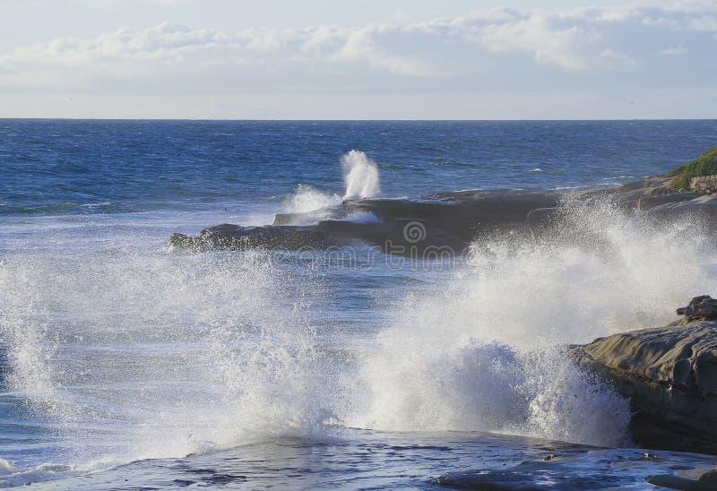 Surf, spray, sea, sky, iconic outcrops at Windansea Beach, La Jolla, CA. Waves break and send up ocean spray over an iconic rock outcrop at Windansea Beach, La royalty free stock image