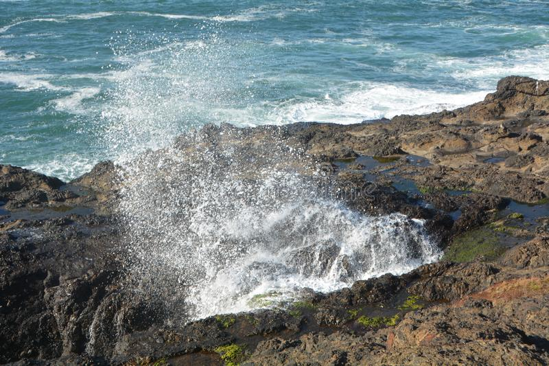 Surf sprays up through rocky shore at Depoe Bay, OR. A burst of surf turns to spray as it is forced through an opening in the rocky shoreline at Depoe Bay stock photo