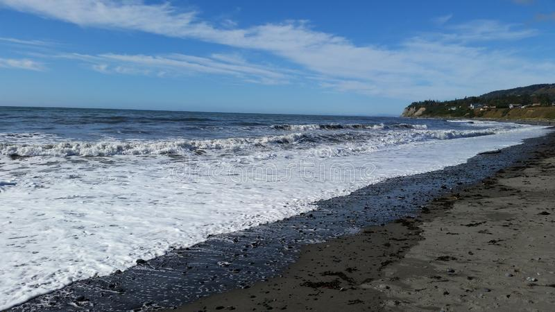 Pacific ocean coastline with surf and sand in Alaska. The surf and tide of the Pacific Ocean in Alaska with blue skies and white clouds stock photography