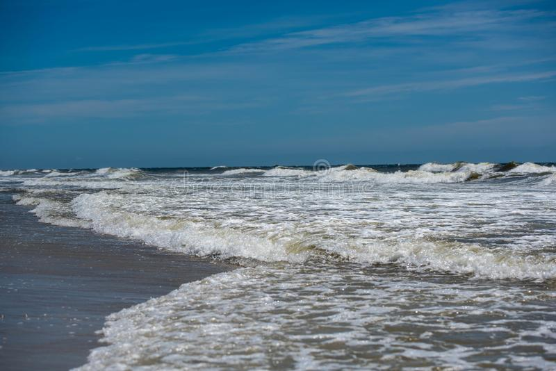 Waves and surf. Surf washing over the beach stock images