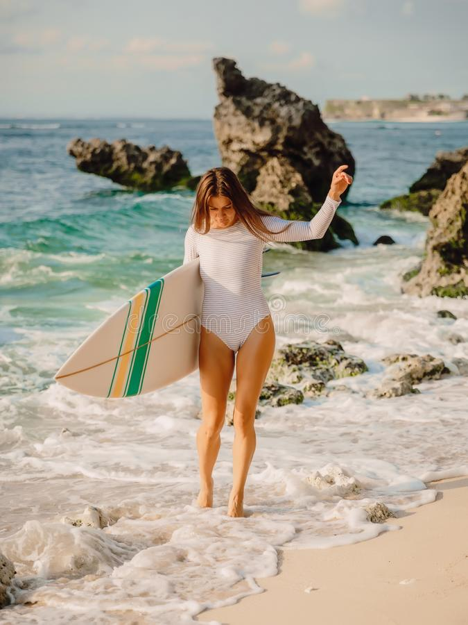 Surf woman with surfboard going to ocean for surfing. Attractive surfer girl. Surf woman with surfboard going to ocean for surfing. Attractive surfer stock photography