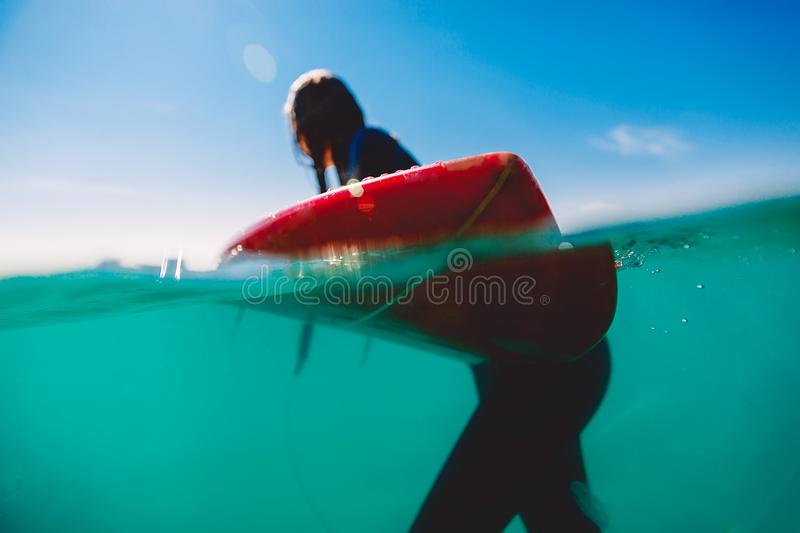Surfer is relaxed with surfboard in ocean. Surfer and ocean. Underwater stock photo