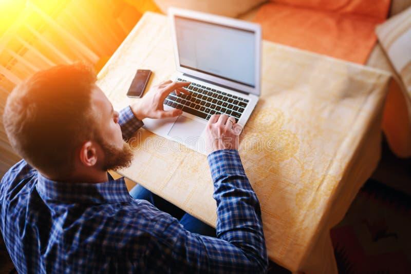 Surfa det netto i regeringsställning Säker ung man som arbetar på bärbara datorn och ler, medan sitta på hans arbetsplats i reger fotografering för bildbyråer