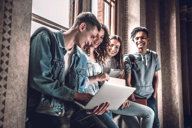 Surfa det netto tillsammans Grupp av lyckliga ungdomarsom tillsammans arbetar och ser bärbara datorn, medan sitta på fönsterfönst royaltyfri bild
