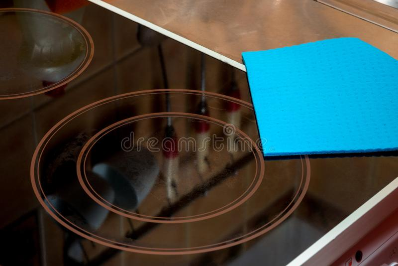 the surface of the ceramic hob and cloth, cleaning the house stock photography