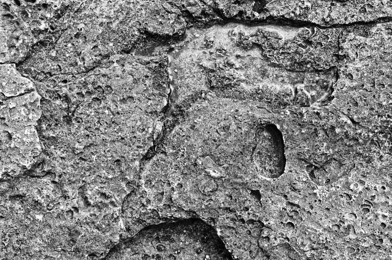 Surface of stone, structure. The surface of the coastal stone in a monochrome representation with a pronounced structure stock images