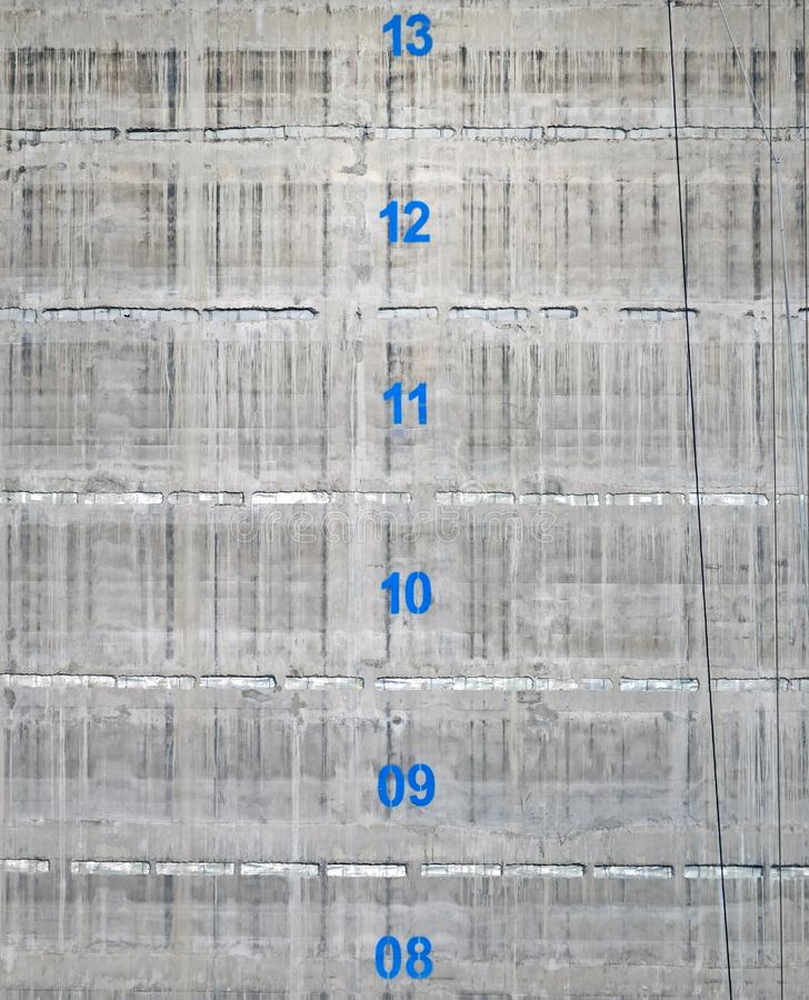 Concrete service tower core of a building under construction with the floor numbers marked in blue paint. The surface of a concrete service tower core of a royalty free stock image