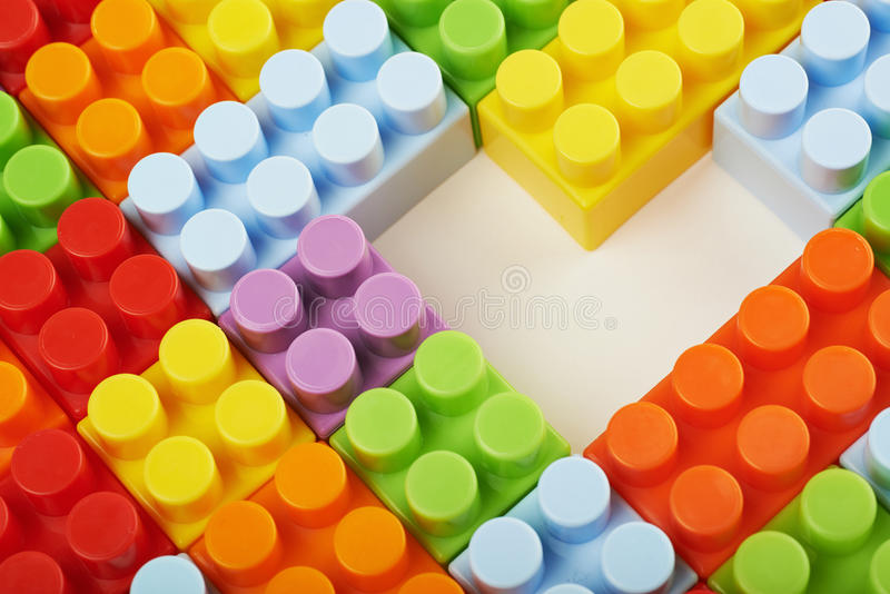Surface covered with toy bricks. Surface covered with plastic and colorful construction toy bricks with a heart shaped gap in the middle, framed as a backdrop stock image