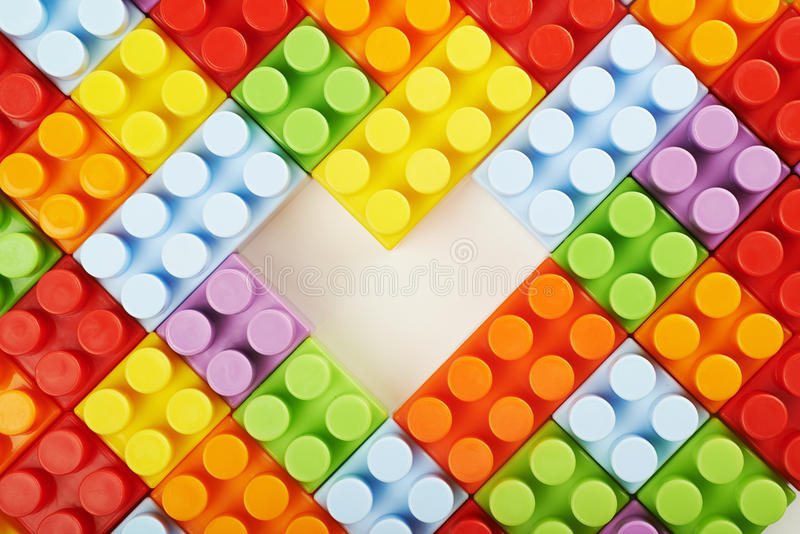 Surface covered with toy bricks. Surface covered with plastic and colorful construction toy bricks with a heart shaped gap in the middle, framed as a backdrop royalty free stock images